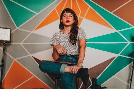 Imagem de uma blogueira sentada perto de uma parede colorida e cheia de formas geométricas