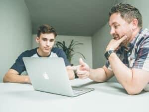 dois homens aprendendo a investir em ações no laptop