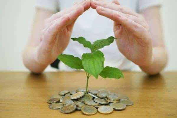 mãos protegendo moedas simbolizando o tema coisas em que você NÃO deve gastar dinheiro