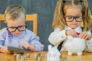Menino e menina com cofrinho e moedas para simbolizar o tema Educação financeira infantil