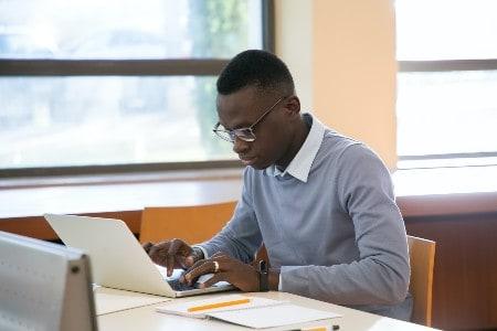 Imagem de um homem sentado e usando o computador fazendo o serviço de clipping, uma das ideias de negócios apresentadas no post