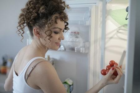 Imagem de uma mulher abrindo a geladeira, representando o conteúdo sobre economia de energia