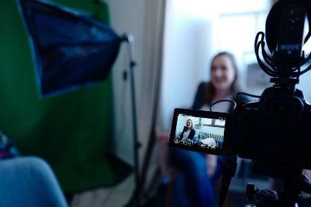 Imagem de uma câmera gravando uma atriz em cena, a profissão de assistente é uma das ideias de negócios interessantes