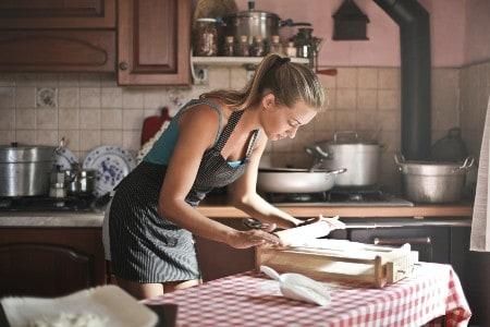 Imagem de uma mulher cozinhando, representando ideias de negócios no ramo alimentício