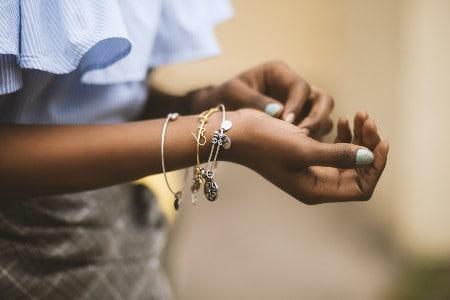 Imagem de uma mulher com várias pulseiras em seu pulso
