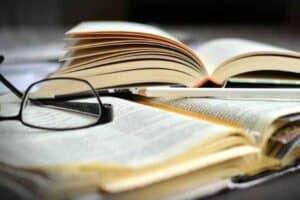 Foto de um livro e óculos sobre a mesa simbolizando o tema Livros para ler