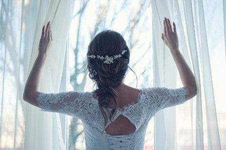Imagem de uma noiva em frente a uma cortina branca