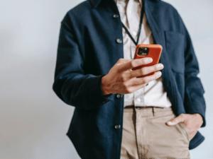 Imagem de um homem usando seu celular para acessar suas contas digitais, uma de suas mãos está no bolso