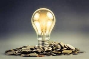 Foto de lâmpada e várias moedas simbolizando o tema Inteligência financeira