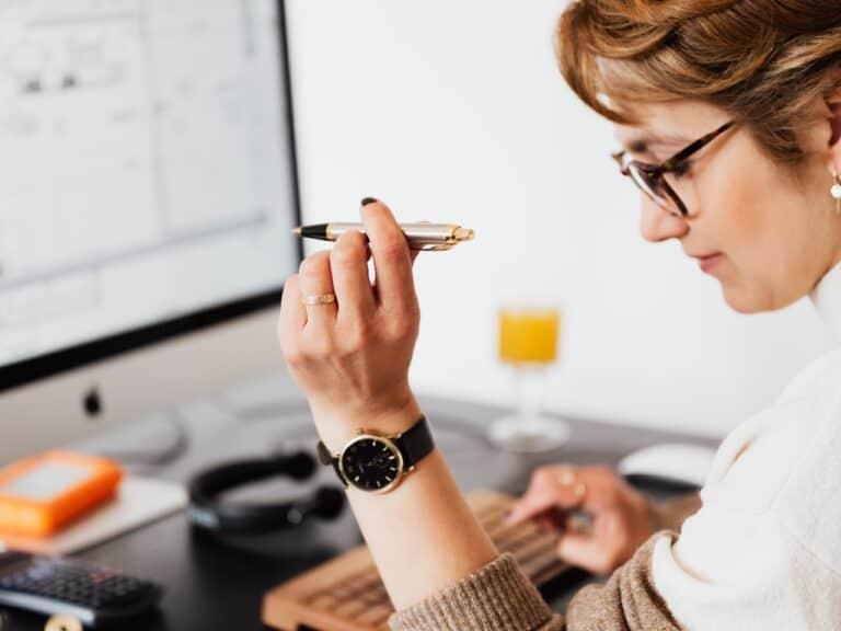 Imagem de uma mulher usando o computador e uma caneta para entender como sair das dívidas rapidamente