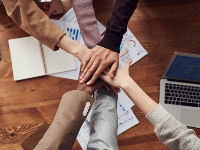 Imagem de várias mãos juntas, representando a união da economia colaborativa