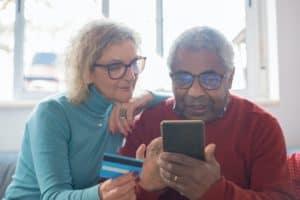 casal idoso segurando cartão de crédito próximo ao celular