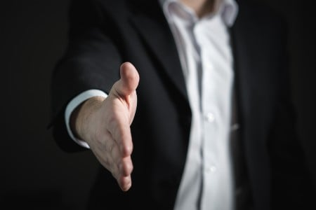 Imagem de uma pessoa estendendo a mão para outra, ilustrando a renegociação como forma de sair das dívidas