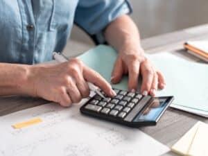 Imagem de um homem com vários papéis e uma calculadora, ilustrando o conteúdo sobre juros do cartão de crédito