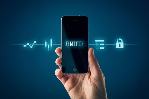 Foto de pessoa segurando um celular com a palavra Fintech na tela