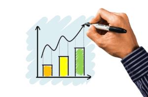 Mão desenhando um gráfico para simbolizar o tema casas de análise de investimentos