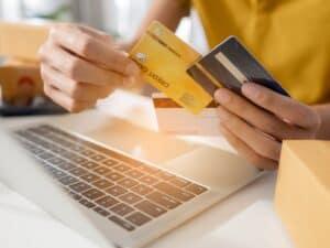 Imagem de uma mulher segurando dois cartões de crédito com um computador em sua frente. Usamos a foto para simbolizar nosso post sobre descobrir o cvv do cartão