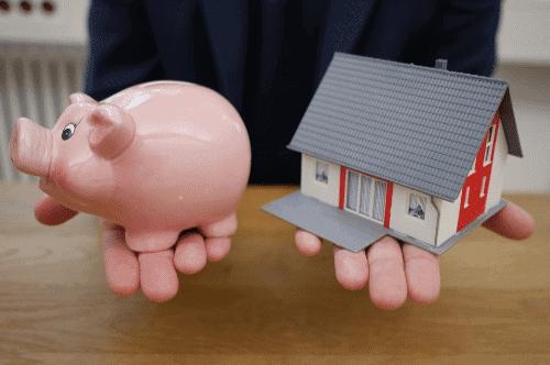 Pessoa segurando cofrinho e miniatura de casa simbolizando o tema Pagar menos juros no financiamento imobiliário