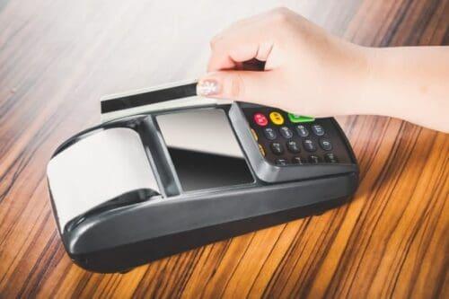 Pessoa passando cartão em máquina para simbolizar o tema melhores cartões de crédito para acumular milhas