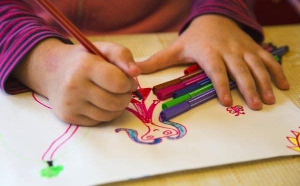 Criança desenhando a mãe em uma folha de papel