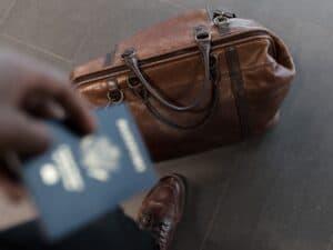 Imagem de uma pessoa com sua mala e passaporte para viajar, ilustrando o conteúdo sobre os Melhores cartões para acumular milhas
