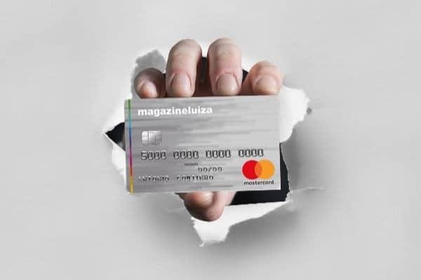 Pessoa segurando o cartão de crédito Magazine Luiza