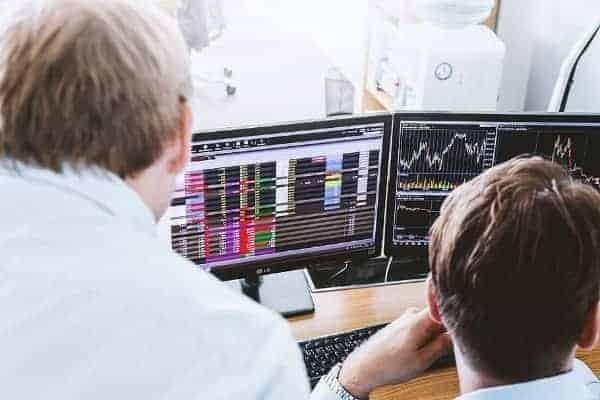 Homens analisando gráficos simbolizando o tema Corretora de valores