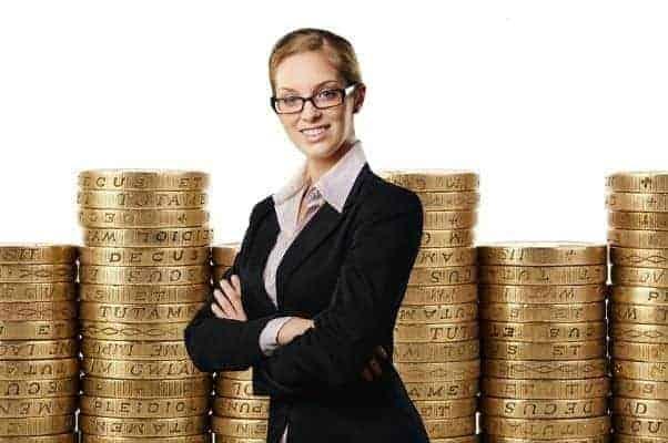 Foto de mulher e muitas pilhas de moedas simbolizando o tema Mulheres mais ricas do Brasil