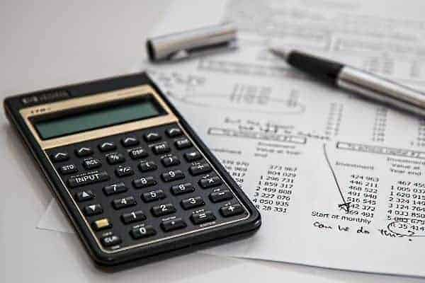 calculadora, papel e caneta simbolizando o tema: adequar o orçamento