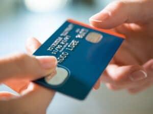 Imagem de uma pessoa entregando um cartão de crédito para outra, simbolizando nosso post sobre como utilizar melhor seu cartão de crédito