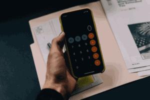 Pessoa usando o celular para calcular se a ação do Serasa vai ajudar a quitar suas dívidas