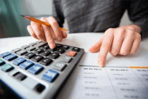 Mulher usando calculadora para simbolizar o tema Cobrança indevida gera dano moral