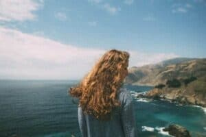 Mulher pegando sol em uma montanha simbolizando o tema Cuidados pessoais
