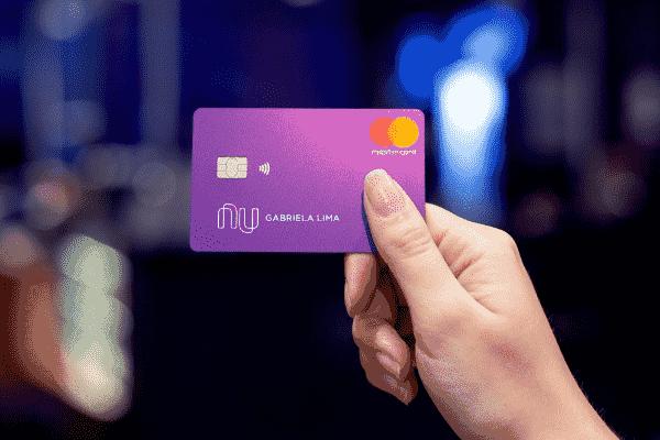 Pessoa segurando o cartão de crédito Nubank para simbolizar o tema Práticas proibidas pelo Nubank