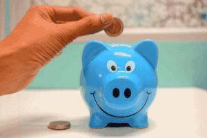 Pessoa colocando moeda em cofrinho para simbolizar o tema Nubank x Poupança