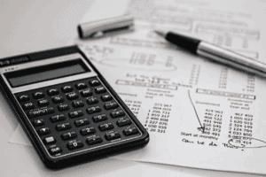 Calculadora, caneta e papel simbolizando os serviços bancários que não funcionam amanhã