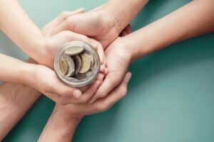 child and parent hands holding money jar, donation, saving, charity, family finance plan concept