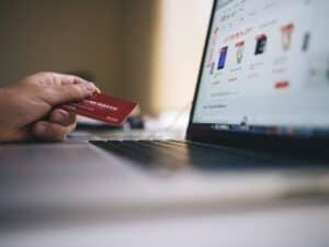 Imagem de uma pessoa fazendo compras no cartão, ilustrando o conteúdo sobre cartão de crédito para negativado