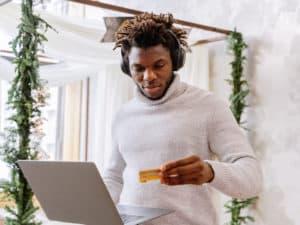 Imagem de um homem segurando um notebook em uma das mãos e um cartão de crédito na outra. Usamos a imagem para ilustrar o post sobre como cancelar o cartão de crédito