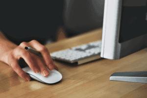 Pessoa utilizando o computador para pesquisar sobre como consultar o score