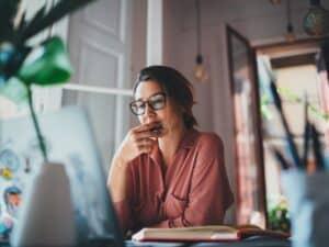 Imagem de uma mulher analisando a tela de um computador. Usamos a imagem para ilustrar o post que ensina como consultar o score