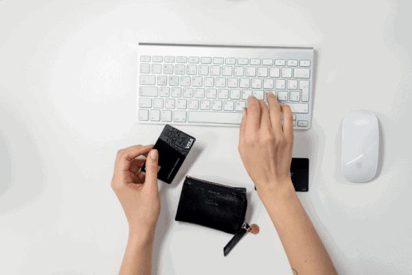 Pessoa no computador ao lado de um cartão de crédito para descobrir o que é o dígito verificador e como encontrá-lo em seu banco