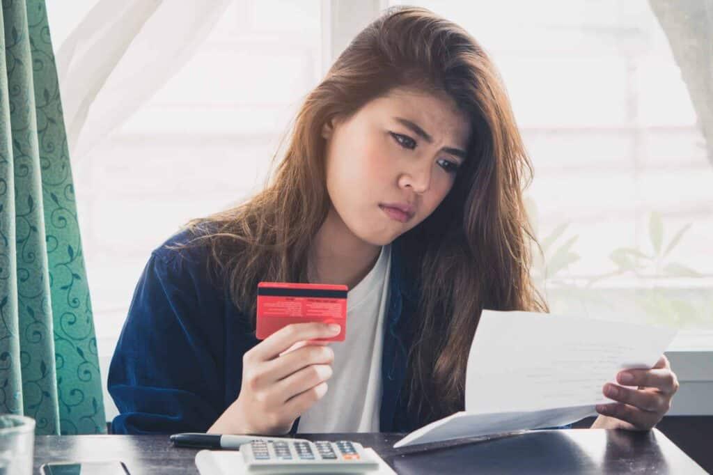 Mulher segurando um papel e um cartão de crédito nas mãos. Usamos a imagem para representar o post sobre juros de atraso do cartão de crédito.