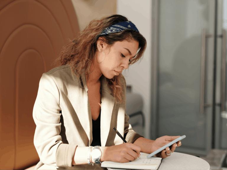Imagem de uma pessoa usando o celular e anotando algo em papéis, ela pode estar buscando sobre empréstimo pessoal