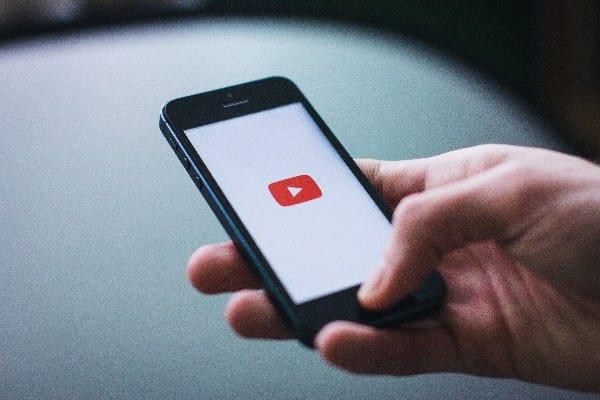 Pessoa abrindo o app do Youtube no celular e pensando como ganhar dinheiro no Youtube