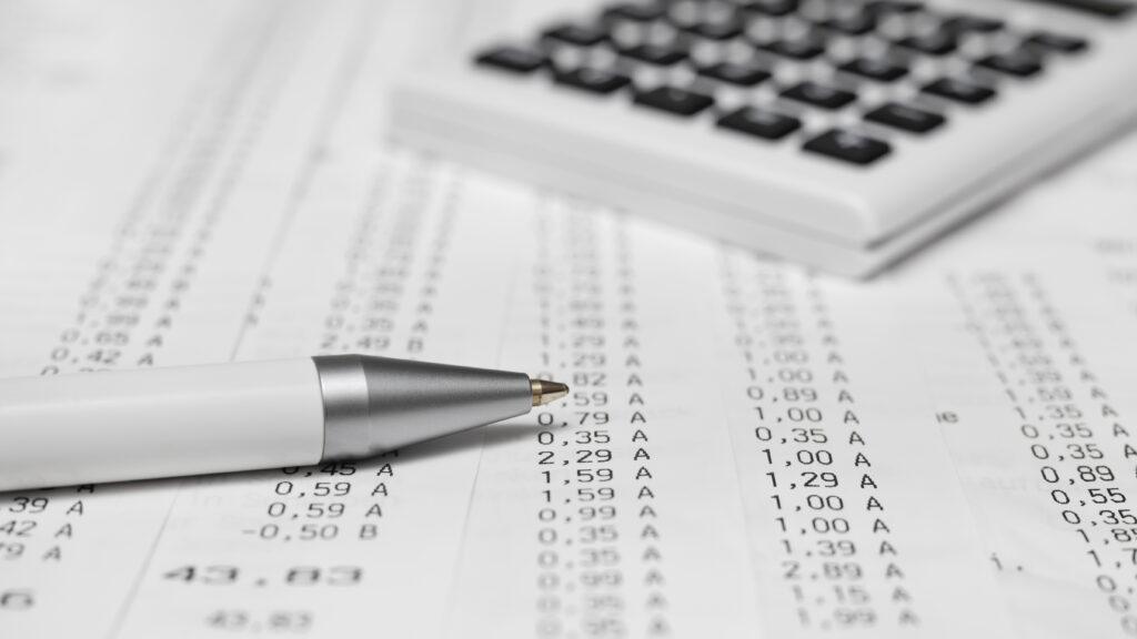 calculadora, caneta e planilha. Cálculo de impostos
