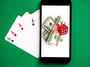 imagem de uma mesa de jogos com um celular em cima e dinheiro na tela para simbolizar jogos para ganhar dinheiro online