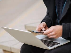 Imagem de uma pessoa usando um notebook e um celular para pesquisar sobre as melhores contas digitais