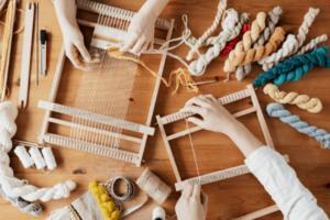 Foto de duas pessoas em uma mesa cheia de tecidos e linhas, descobrindo o que é DIY de forma prática