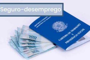 imagem de uma carteira de trabalho com notas de cem reais em volta, para ilustrar o tema: consulta de habilitação do seguro-desemprego
